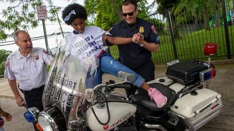 Zuroni Beckett, 9, sits on a police motorcycle