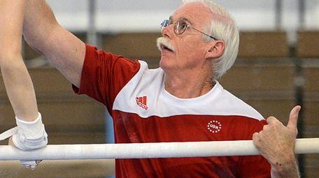 Coach John Holman helps Allentown Parkettes gymnast Christina