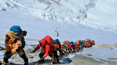 A long queue of mountain climbers line a
