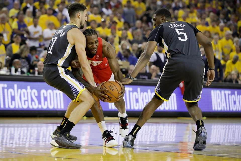 Toronto Raptors forward Kawhi Leonard, middle, drives between