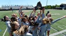 Mattituck/Southold players lift the championship plaque after the