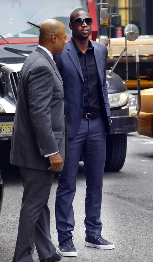 Miami Heat's Dwyane Wade, right, arrives for a