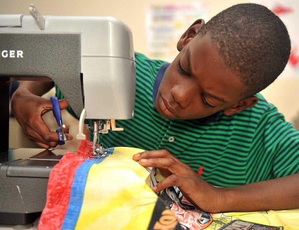 Darit Rains, 10, makes pillow cases as part