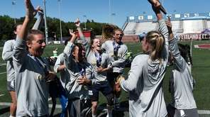 Eastport-South Manor players celebrate with the championship plaque