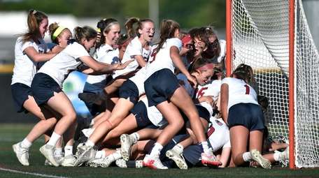 Cold Spring Harbor players storm the field after