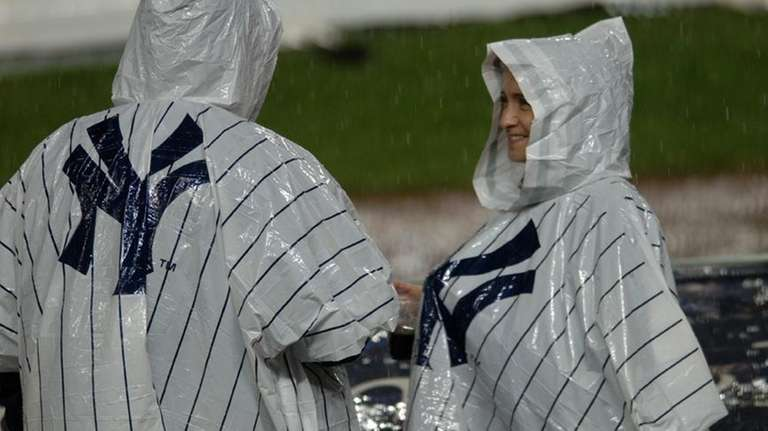 Two fans attempt to stay dry at Yankee