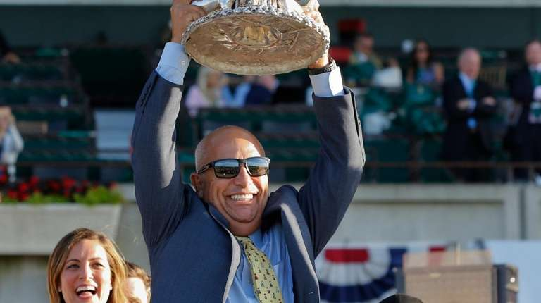 Sir Winston trainer Mark Casse lifts up the