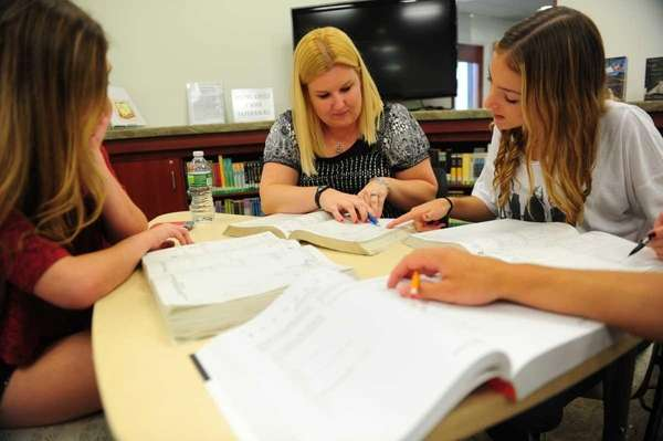 SAT tutor Amy Fortsch, center, coaching students Laura