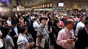 Passengers wait at Penn Station as LIRR service