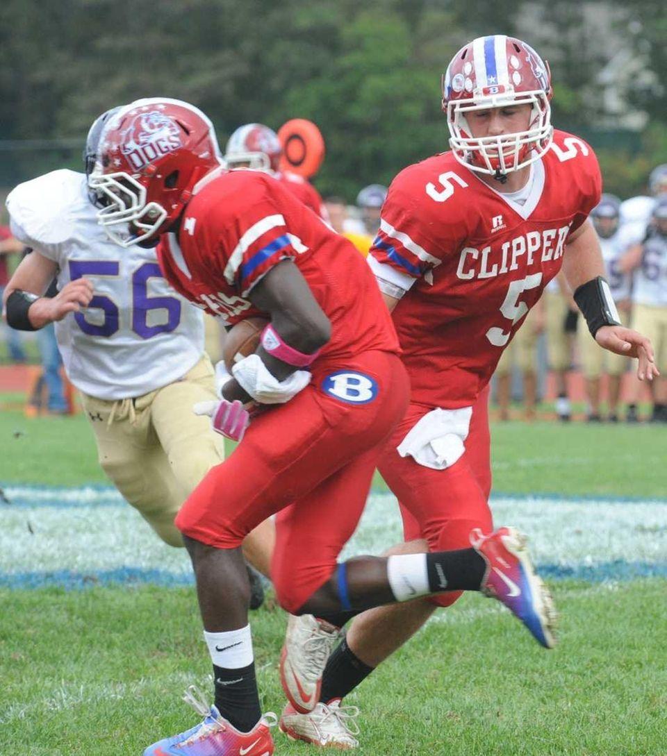 Bellport quarterback Justin Honce handing the ball to