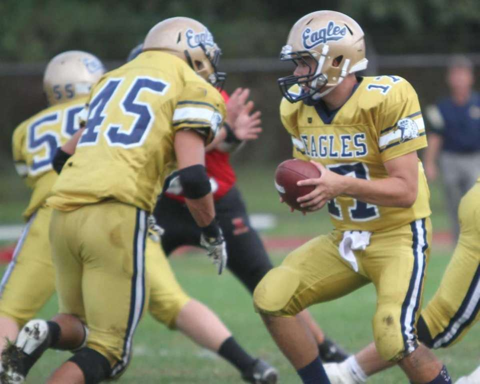 Bethpage quarterback Justin Rohr hands off to running