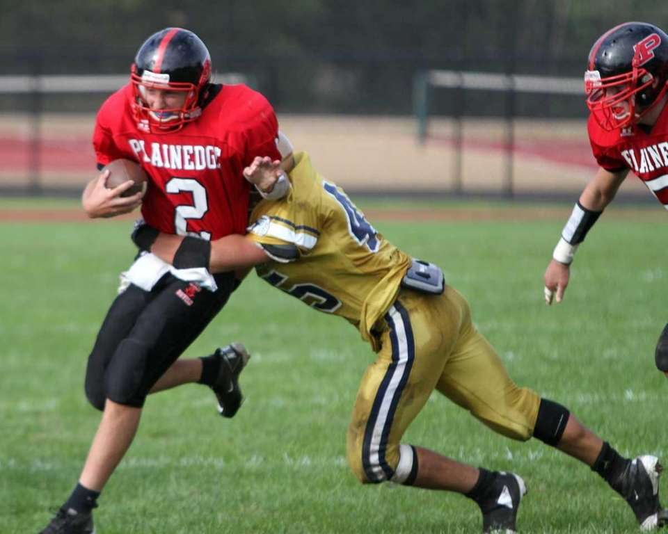 Plainedge quarterback Nick Frenger is wrapped up by