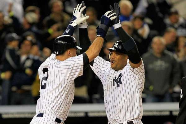 Robinson Cano is congratulated by Derek Jeter after