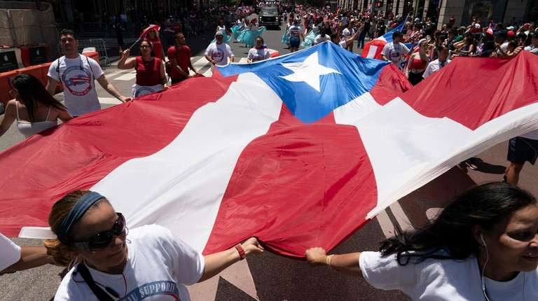 A large Puerto Rican flag is carried on