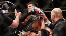 Henry Cejudo celebrates with his team after defeating