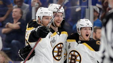 Boston Bruins defenseman Brandon Carlo, center, celebrates with