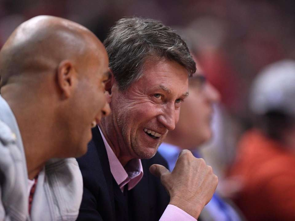 Hockey great Wayne Gretzky laughs as watches play