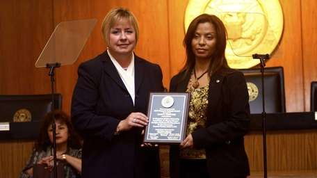 Nancy Fuentes, right, is presented with the Town