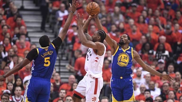 Raptors forward Kawhi Leonard shoots under pressure from