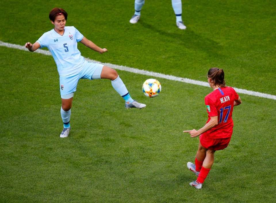United States' Tobin Heath, right, kicks the ball