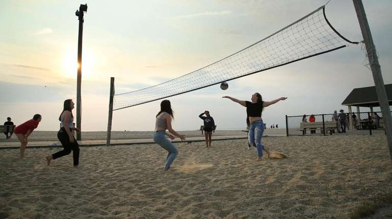 Young people play volleyball at West Meadow Beach