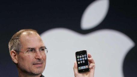 Apple chief executive Steve Jobs holds up an