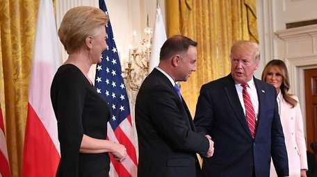 President Donald Trump shakes hand with Poland's President