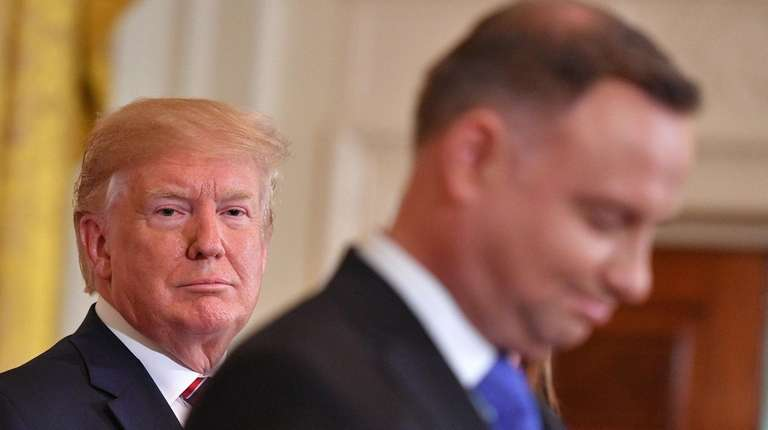 President Donald Trump listens while Polish President Andrzej