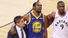 Kevin Durant of the Warriors is assisted off