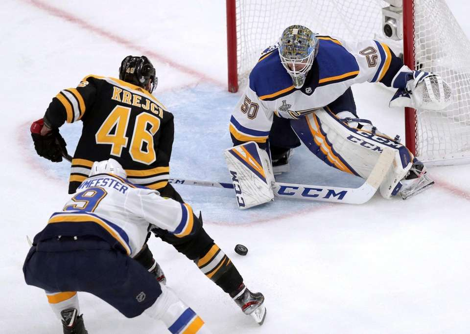 St. Louis Blues goaltender Jordan Binnington, right, defends