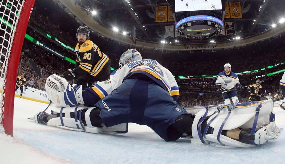 St. Louis Blues goaltender Jordan Binnington, foreground, defends