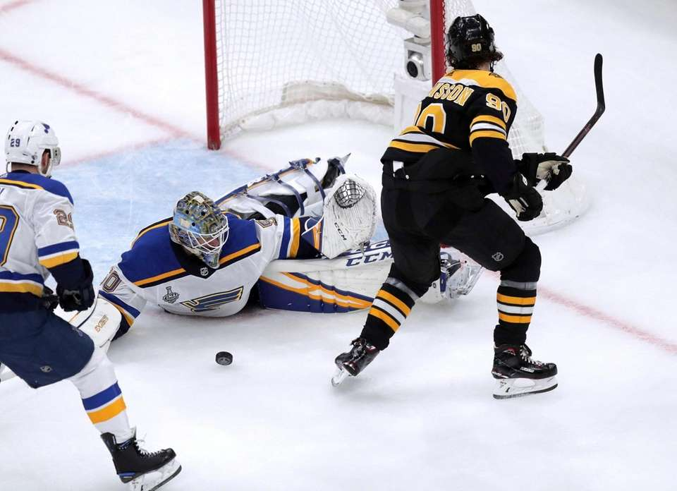 St. Louis Blues goaltender Jordan Binnington, left, stops