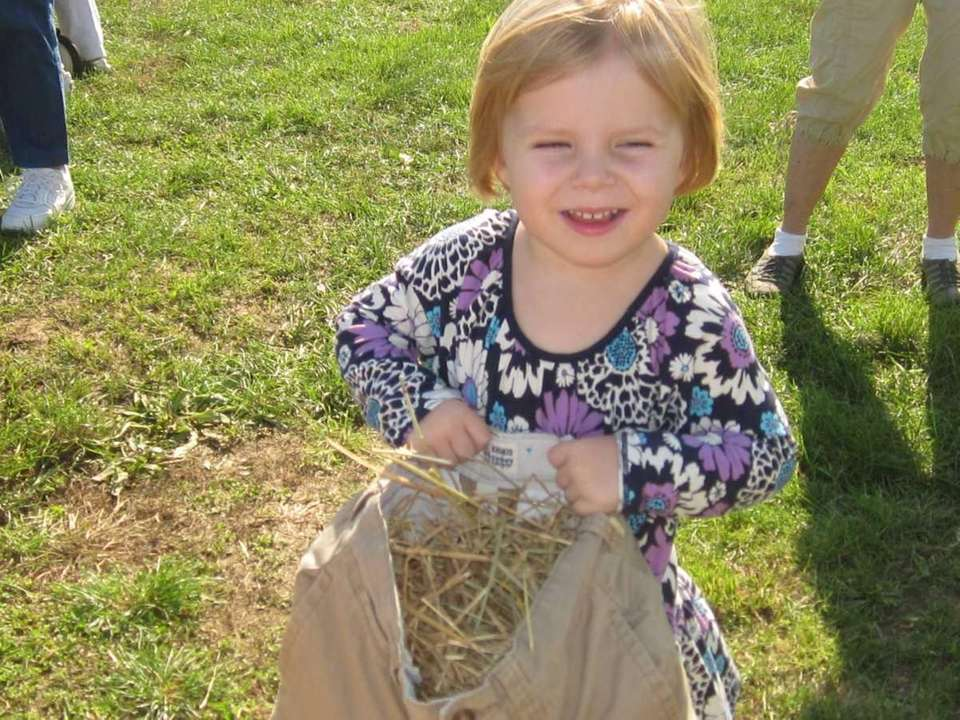 Chloe Shaner, 2, of Brooklyn dresses a scarecrow