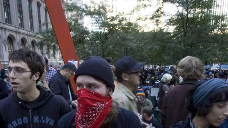 Demonstrators holding signs gather at the Occupy Wall