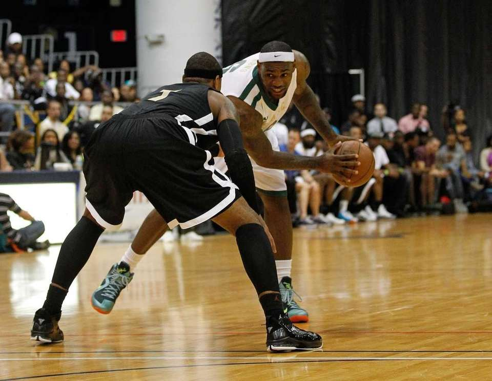 LeBron James (R) posts up Carmelo Anthony during