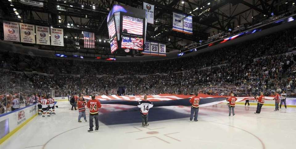 FDNY and NYPD hockey team players hold the