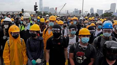 Protestors wear masks and helmets to protect their