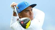 Rickie Fowler plays a shot from the 14th