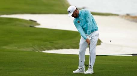 Louis Oosthuizen, of South Africa, hits a chip
