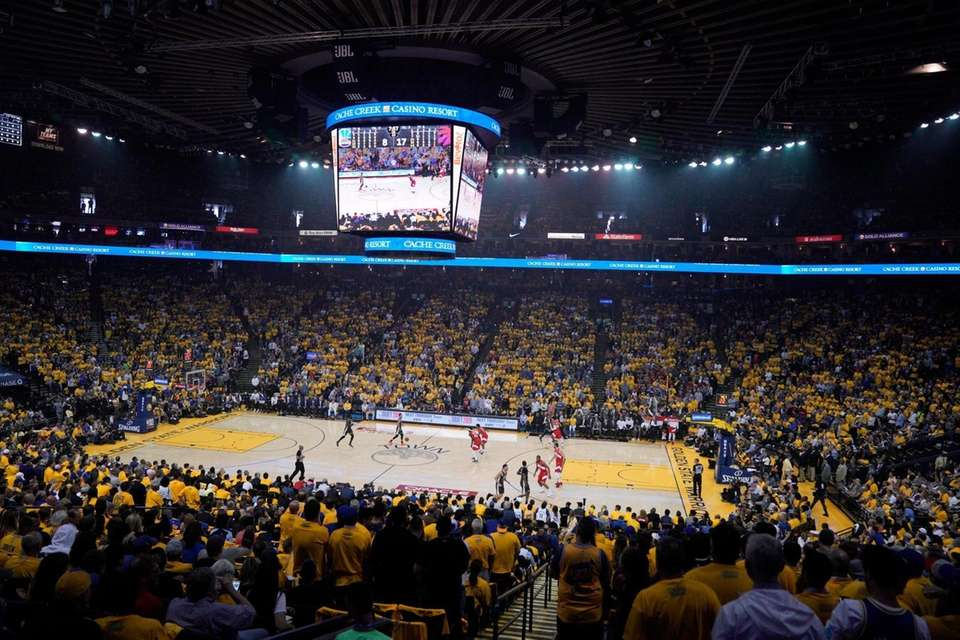 Fans at Oracle Arena watch during the first
