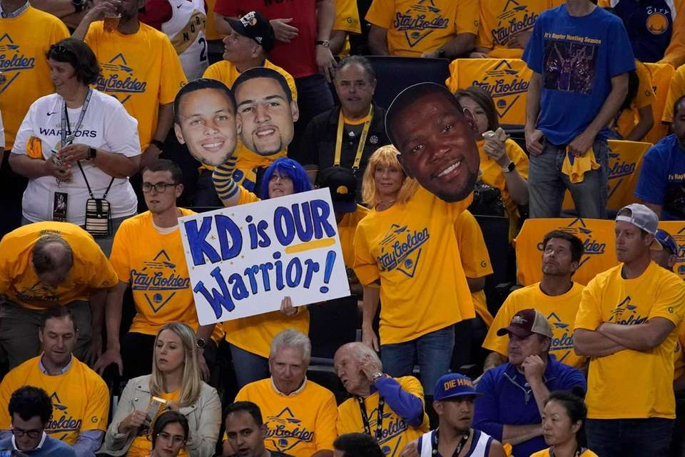 Fans hold up signs for injured Golden State