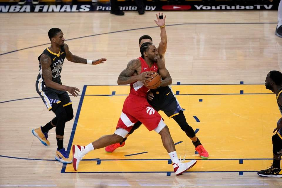 Toronto Raptors forward Kawhi Leonard, foreground, drives against
