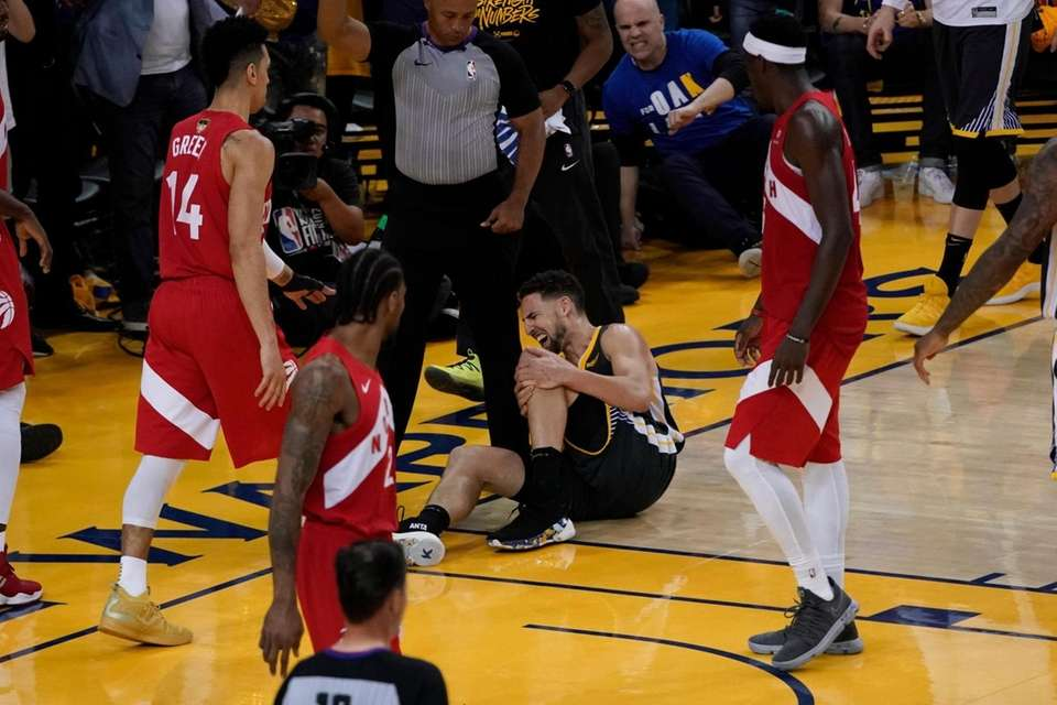 Warriors guard Klay Thompson, center, reacts after what