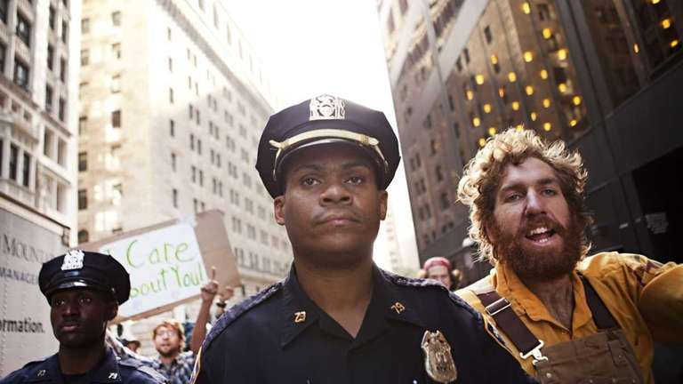 Officers walk near a Occupy Wall Street protester.