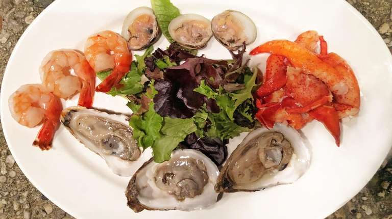A cold seafood platter with oysters, clams, shrimp