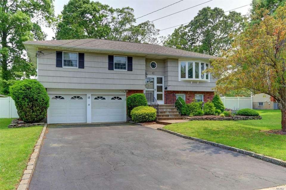 This East Islip high-ranch includes four bedrooms and