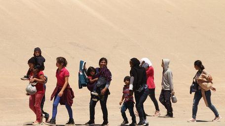 Central American migrants cross the Rio Grande in