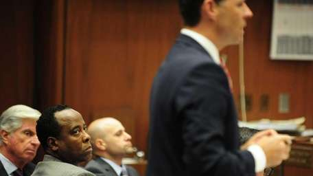 Dr. Conrad Murray, second from left, listens as
