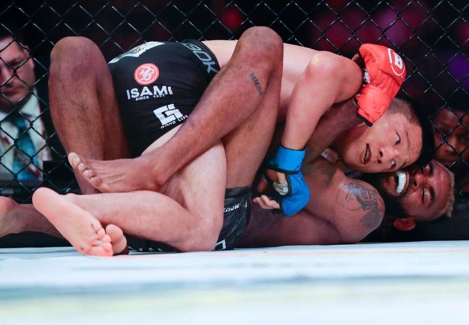 Japan's Kyoji Horiguchi, top, grapples with Darrion Caldwell