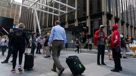 People walk on May 16 at Seventh Avenue